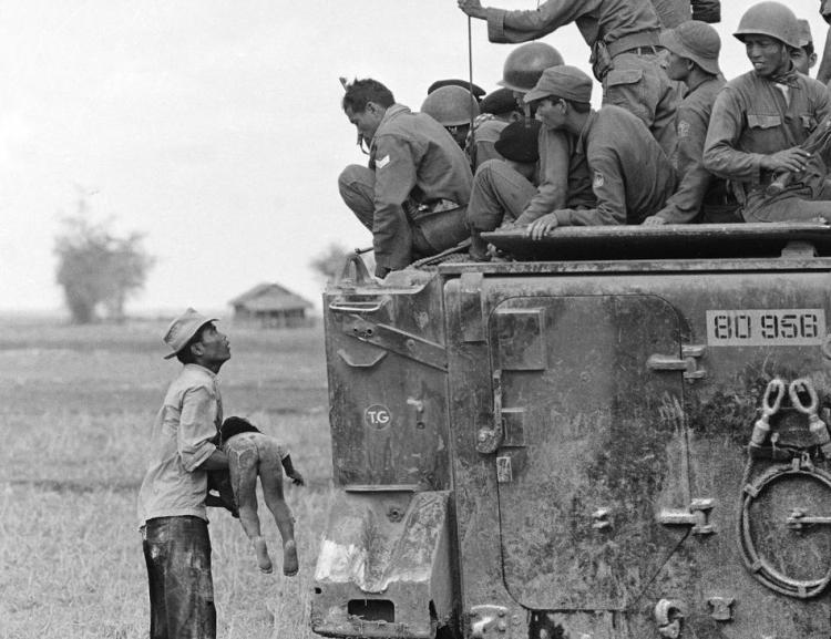 A father holds the body of his child as South Vietnamese Army Rangers look down from their armored vehicle March 19, 1964. The child was killed as government forces pursued guerrillas into a village near the Cambodian border. (AP Photo/Horst Faas)