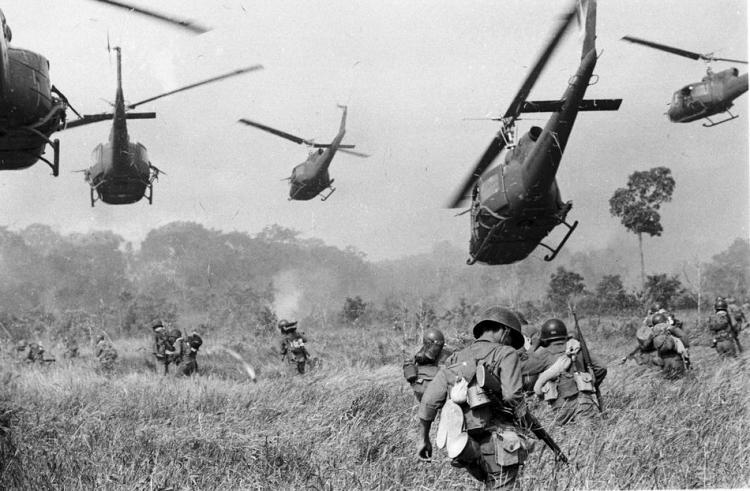 Hovering U.S. Army helicopters pour machine gun fire into a tree line to cover the advance of South Vietnamese ground troops in an attack on a Viet Cong camp 18 miles north of Tay Ninh, northwest of Saigon near the Cambodian border, in Vietnam in March of 1965. (AP Photo/Horst Faas, File)