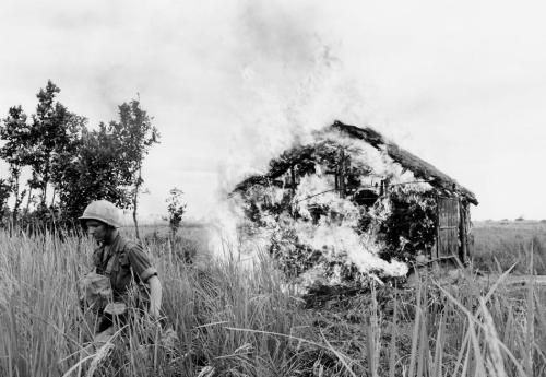 "A U.S. paratrooper moves away after setting fire to house on bank of the Vaico Oriental River, 20 miles west of Saigon on Jan. 4, 1966, during a ""scorched earth"" operation against the Viet Cong in South Viet Nam. The 1st battalion of the 173rd airborne brigade was moving through the area. (AP Photo/Peter Arnett)"