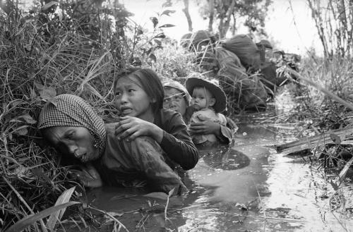 Women and children crouch in a muddy canal as they take cover from intense Viet Cong fire at Bao Trai in Jan. of 1966, about 20 miles west of Saigon, Vietnam. (AP Photo/Horst Faas, File)