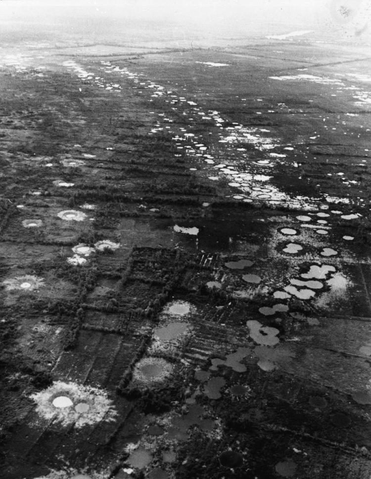 Water-filled bomb craters from B-52 strikes against the Viet Cong mark the rice paddies and orchards west of Saigon, Vietnam, 1966. Most of the area had been abandoned by the peasants who used to farm on the land. (AP Photo/Henri Huet)